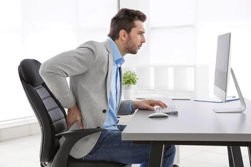 homem sentado com dor na zona lombar